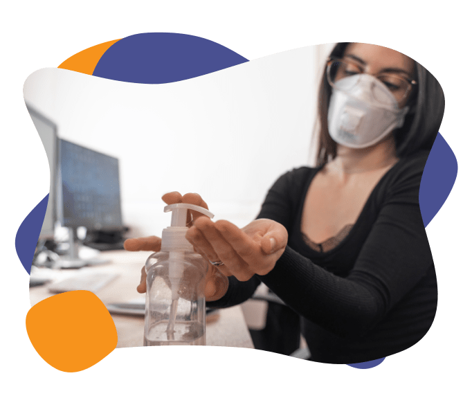 A woman wearing a mask applies hand sanitizer
