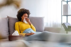 woman on couch with allergies using kleenex tissues